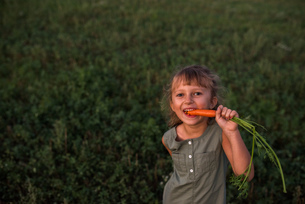Portrait of young girl, eating freshly picked carrotの写真素材 [FYI03572613]