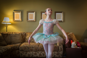Young girl practising ballet moves in living roomの写真素材 [FYI03572620]