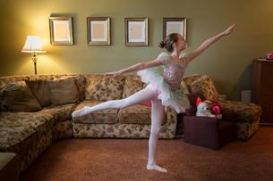 Young girl practising ballet moves in living roomの写真素材 [FYI03572621]