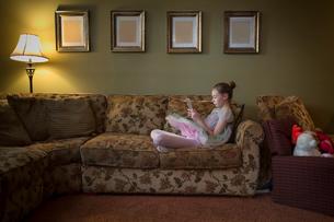 Young girl sitting crossed legged on sofa readingの写真素材 [FYI03572622]