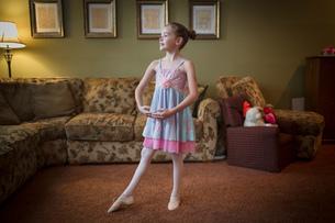 Young girl practising ballet moves in living roomの写真素材 [FYI03572623]