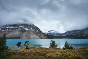 Hikers hiking by lake and snow capped mountains, Banff, Alberta, Canadaの写真素材 [FYI03572766]