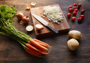 Fresh carrots, potatoes and cherry tomatoes with onions chopped on cutting boardの写真素材 [FYI03572845]