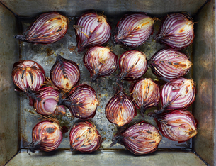 Overhead view of roasted red onion halves with rosemary and olive oil in roasting tinの写真素材 [FYI03572849]