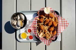 Overhead view of fried seafood and french fries on tray with bowl of scallops, Lunenburg, Nova Scotiの写真素材 [FYI03572857]