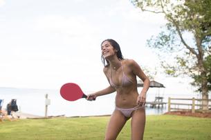 Young woman in bikini playing table tennis at coast, Santa Rosa Beach, Florida, USAの写真素材 [FYI03572867]