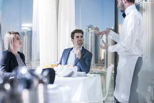 Businessman and woman at breakfast in hotel restaurantの写真素材 [FYI03572899]