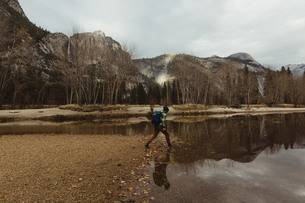Male hiker hiking by lake, Yosemite National Park, California, USAの写真素材 [FYI03572939]