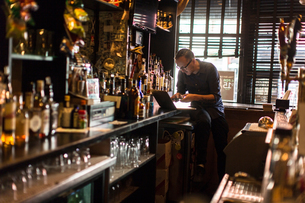 Barman typing on laptop at public house counterの写真素材 [FYI03572957]
