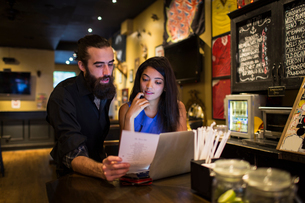 Young couple reading menu at public house tableの写真素材 [FYI03572962]
