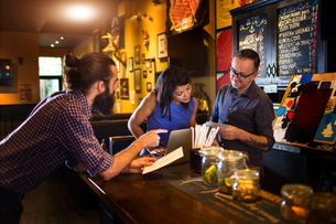 Barman reading menu with young couple at public house counterの写真素材 [FYI03572965]