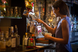 Barmaid using cash register in public houseの写真素材 [FYI03572971]
