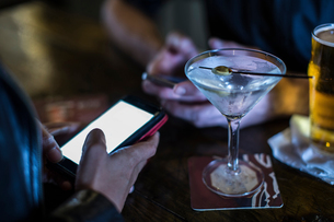 Close up of female hand using smartphone in public houseの写真素材 [FYI03572979]