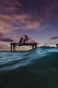 Silhouette of friends bouncing on trampoline in sea, Oahu, Hawaii, USAの写真素材 [FYI03573069]