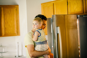 Father holding young son, looking in fridgeの写真素材 [FYI03573231]