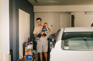 Father holding son in garageの写真素材 [FYI03573256]