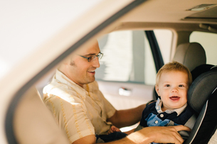 Father securing young son in car seatの写真素材 [FYI03573258]
