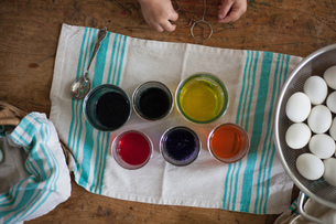Overhead view of girl's hands preparing to dye easter eggs at tableの写真素材 [FYI03573268]