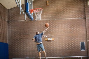 Tattooed man jumping and aiming ball toward basketball net on courtの写真素材 [FYI03573314]