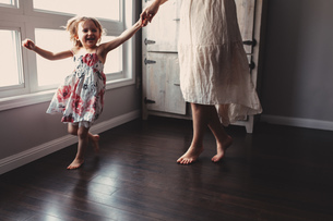 Cute girl running barefoot in house with motherの写真素材 [FYI03573337]