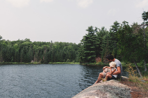 Young man and daughter sitting on rock at the edge of a lakeの写真素材 [FYI03573344]
