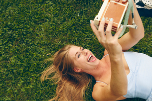 Young woman lying on grass taking selfie with retro cameraの写真素材 [FYI03573375]