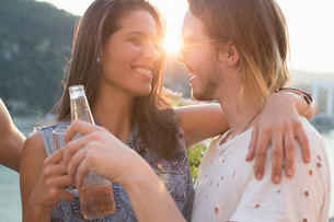 Happy young couple at sunset roof terrace party, Budapest, Hungaryの写真素材 [FYI03573409]