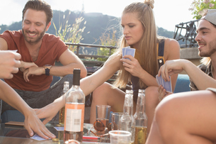 Adult friends playing cards at roof terrace partyの写真素材 [FYI03573477]