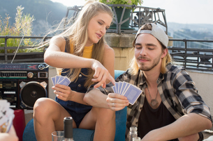 Young couple playing card game at roof terrace party, Budapest, Hungaryの写真素材 [FYI03573478]