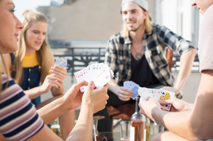 Young adults playing card game at roof terrace party, Budapest, Hungaryの写真素材 [FYI03573479]