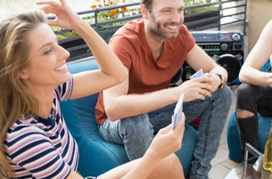 Young adult friends playing card games at roof terrace partyの写真素材 [FYI03573480]