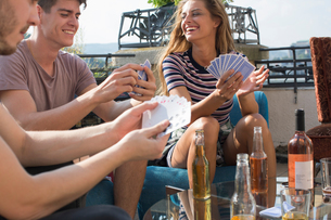 Adult friends playing card games at roof terrace partyの写真素材 [FYI03573487]