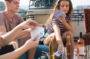 Young adult friends playing card games at roof terrace partyの写真素材 [FYI03573488]