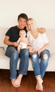 Portrait of parents sitting on sofa with baby sonの写真素材 [FYI03573489]