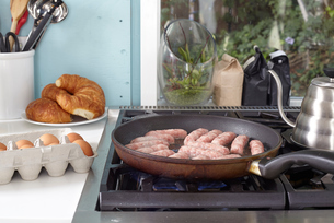 Breakfast sausages frying in pan on hobの写真素材 [FYI03573490]