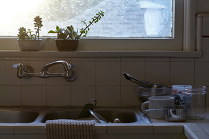 Dirty washing up stacked in kitchen sink and counterの写真素材 [FYI03573491]