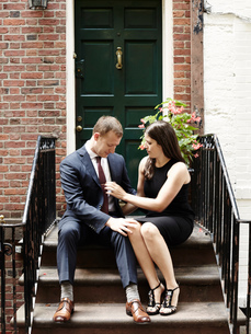 Young couple sitting on steps, woman adjusting man's neck tieの写真素材 [FYI03573514]