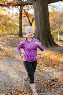 Senior woman exercising, running, in rural settingの写真素材 [FYI03573517]