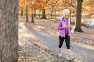 Senior woman walking outdoors, using smartphone, wearing earphones and holding water bottleの写真素材 [FYI03573518]