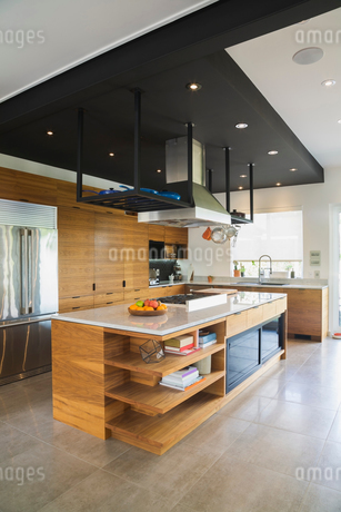 Kitchen with American walnut wood island, cabinets and quartzite countertops inside a modern cube stの写真素材 [FYI03573563]