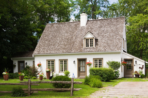 Old (circa 1886) white with beige and brown trim Canadiana cottage style home facade in summer, Quebの写真素材 [FYI03573575]