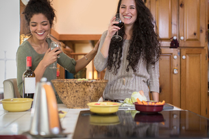 Two female friends preparing salad and laughing at kitchen counterの写真素材 [FYI03573627]