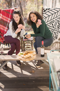 Two young female friends laughing, playing card game on patioの写真素材 [FYI03573643]