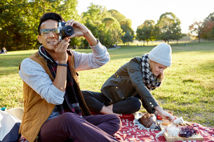 Mid adult man with girlfriend taking photographs during park picnicの写真素材 [FYI03573664]