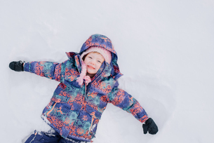 Girl lying down in snowの写真素材 [FYI03573696]