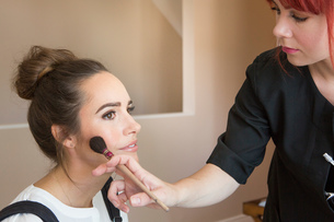 Make up artist applying blusher to female fashion and lifestyle bloggerの写真素材 [FYI03573718]
