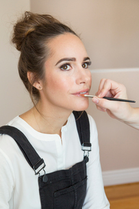 Hand of make up artist applying lip gloss to female fashion and lifestyle bloggerの写真素材 [FYI03573719]