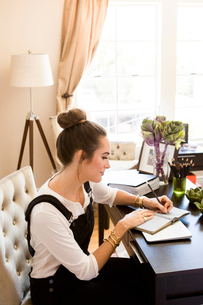 Female fashion and lifestyle blogger writing in notebook at deskの写真素材 [FYI03573720]