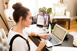 Female fashion and lifestyle blogger typing on laptop at deskの写真素材 [FYI03573722]