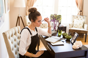 Female fashion and lifestyle blogger contemplating notebook at deskの写真素材 [FYI03573723]